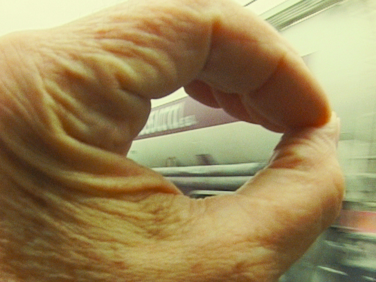 """Agnès Varda's hand is in the foreground, thumb and index finger forming a circle, through which she views a truck passing her on the highway in a still from her 2000 film, """"The Gleaners and I."""""""